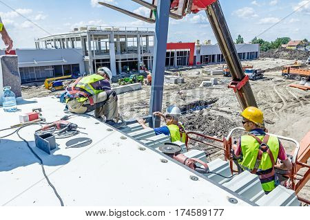 Zrenjanin Vojvodina Serbia - June 29 2015: High elevated cherry picker with people is working at new assembled canopies on construction site.