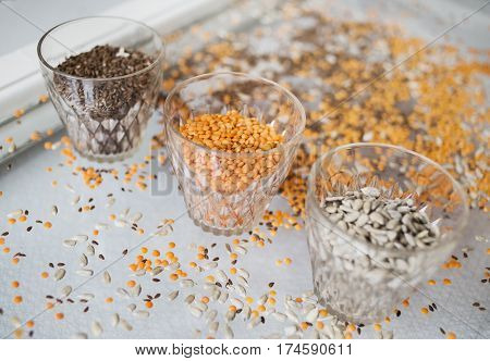 Flaxseeds, red lentils and sunflowers in different glasses, standing on an old window glass