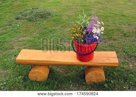 Various summertime wild flowers bouquet on yellow wooden bench in garden