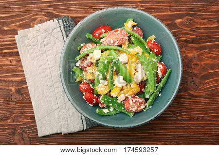 Snow pea salad with feta, tomato and pepper. Low fat healthy eating concept.