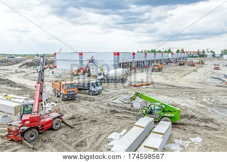 Landscape transform into urban area with machinery people are working. View on construction site.
