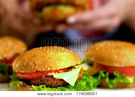 Hamburger fast food with ham on wooden board for friend party. Close up of group of hamburger on blurred background. Piece of cheese hanging from sandwich. Human hand touch cheeseburger is not in