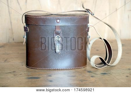 Vintage  brown color binoculars closed hard leather carry case on wooden background front view indoor closeup