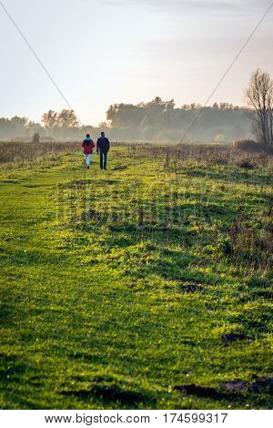 A man and a woman walking together in a Dutch nature reserve. It is at the end of an autumn day the sun is low and there's some haze in the distance across the landscape.