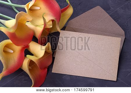 Red And Yellow Calla Lily Flowers With Envelope On Plaster Gray Background. Copy Space.