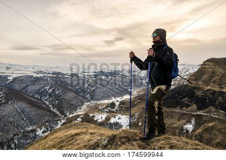 Young bearded hipster wearing a hat and sunglasses with Nordic walking sticks and a backpack moves in the mountains at sunset, against a background of sunset sky and an extinct volcano Elbrus