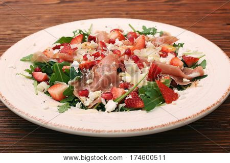 Arugula salad with strawberries, feta cheese, prosciutto, parmesan and pomegranate. Healthy low fat eating concept.