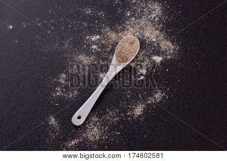 White whole-wheat flour and a spoon on a black background