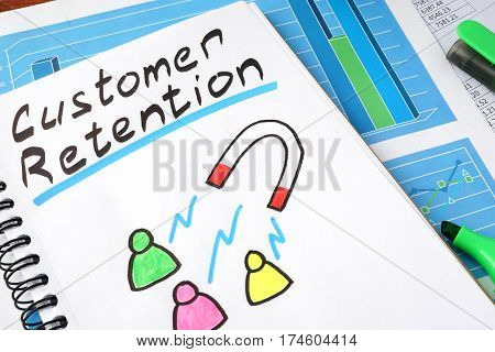 Customer retention written in a notebook and marker.