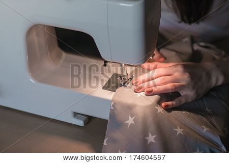 Women's hands behind her sewing. Sewing process with leather