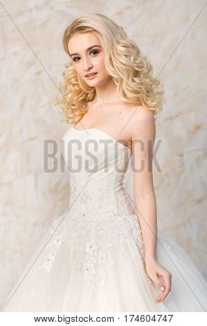 Portrait of the gorgeous smiling blonde bride with beautiful curly hair in a white wedding dress closeup on a light background. beautiful young model with bridal hairstyle and makeup in a white magnificent dress.