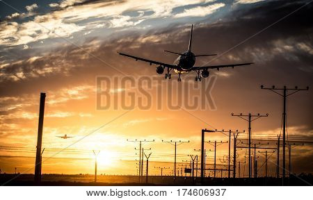 Airplane landing on the track. Dramatic warm toned sky