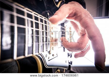 Rock band in action. guitarist playing close up