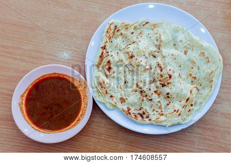 Roti canai or roti Prata with curry sauce.This is the famous authentic recipe used by the Indians in Malaysia.