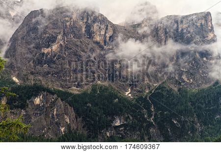 Pisciadu waterfall and Sella mount from Colfosco on a foggy day Val Badia Italy
