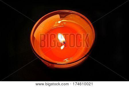 Bright orange burning candle in the dark