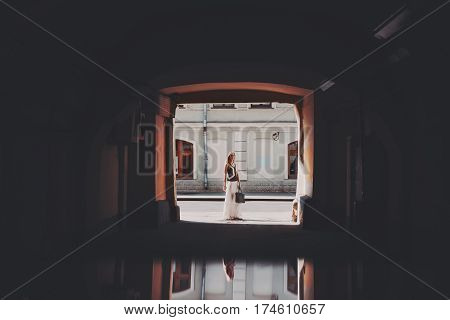 Beautiful adult blonde woman in sunglasses and long skirt is standing with bag in the end of long dark tunnel with reflective floor on sunny day city road and wall of residential house in background