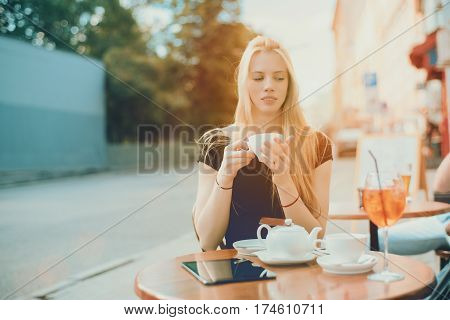 Young beautiful dreamy woman drinking tea while sitting in street cafe charming pensive blonde lady thinking about something during morning breakfast in street bar with teapot and glass of spritz