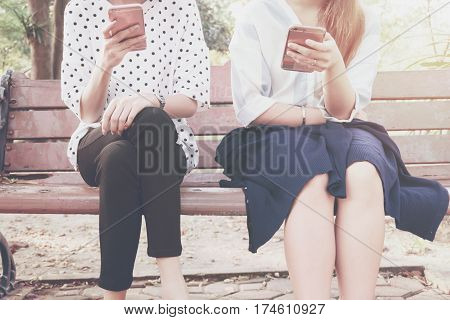 Two women in disinterest moment with smart phones in the outdoor concept of relationship apathy and using new technology and smartphone addiction. vintage tone
