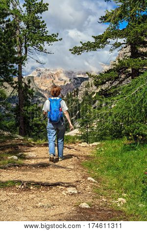 Woman walks on a trail in Badia Valley Alto Adige Italy