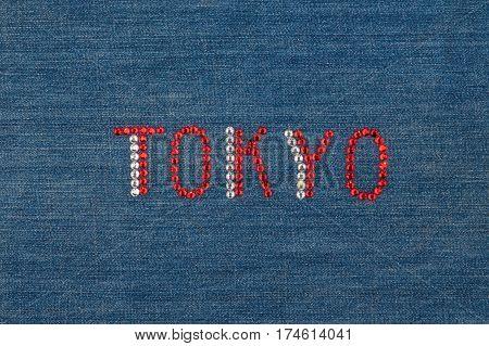 Inscription Tokyo inlaid rhinestones on denim. View from above