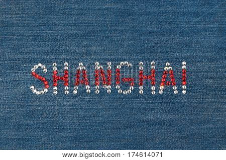 Inscription Shanghai inlaid rhinestones on denim. View from above