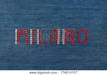 Inscription Milano inlaid rhinestones on denim. View from above