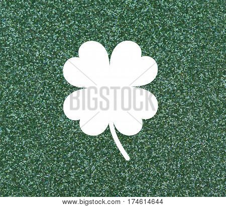 Clover with four leaves White on a glittery green background.