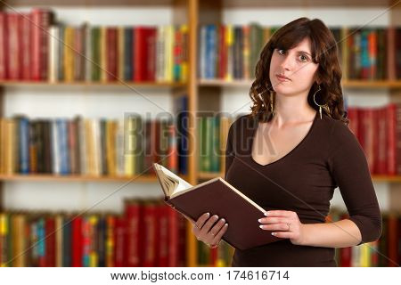 Portrait of clever student with book reading it in college library