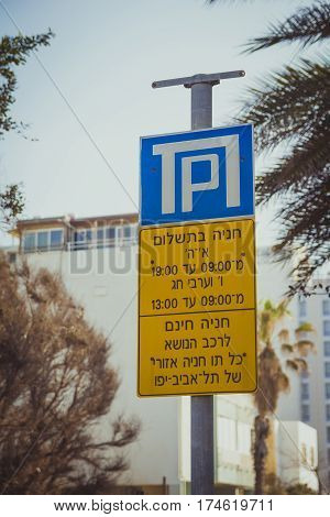 Parking sign in the city of Tel Aviv Israel. These things are written in Hebrew on the sign: Parking fee. Sunday through Thursday from 9:00-19:00. Fridays and holiday eves 9:00-13:00. Free parking for cars with a parking badge of Tel Aviv city.