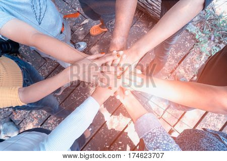 Business teamwork hands together joining group of people in circle with sun ray light and lens flare. - Concepts collaborate team and projects process to success.