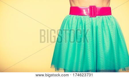 Woman fahion accessories clothing concept. Close up of pink belt on blue turquoise tulle skirt
