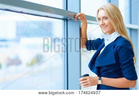 Yound woman drink coffee at office, standing