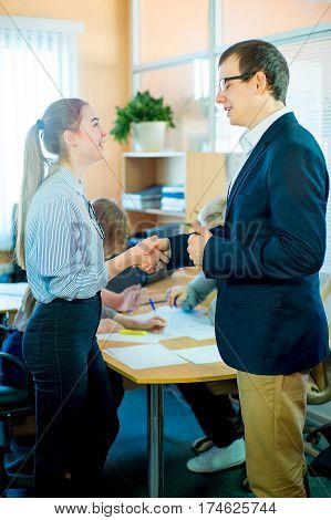 business team discussing at a table in an office, new business ideas. Two young men and two girls with glasses. business woman and business man shaking hands