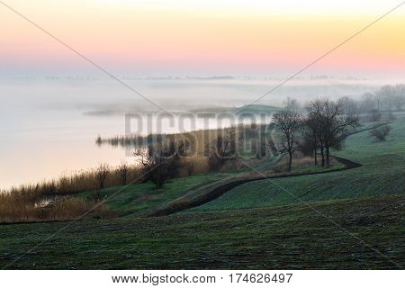 Idyllic Countryside Morning Landscape with freshly tilled agricultural Field Fog over River and Sunrise
