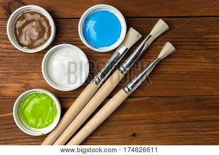Brush and colorful paint in jars on an old wooden background with copy space
