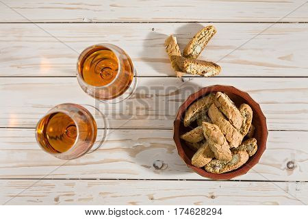 Italian cantucci biscuits and two glasses of vin santo wine on a table seen from above