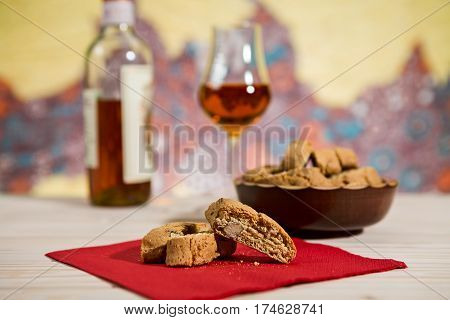Closeup of Italian cantucci biscuits on a red napkin and vin santo wine on background