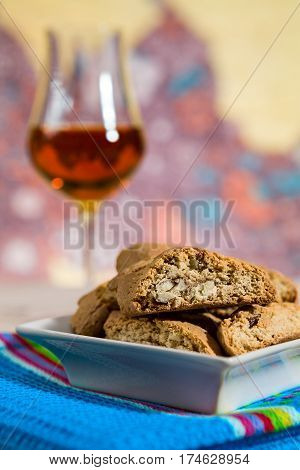 Closeup of Italian cantucci biscuits on a blue napkin and a glass of vin santo wine on background