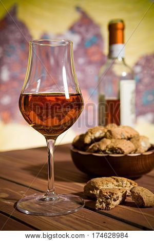 Closeup of a glass of Italian vin santo wine and cantucci biscuits on a wooden table