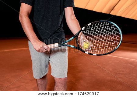 Man in t-shirt with racket on indoor tennis court. Play tennis. Ball in hand