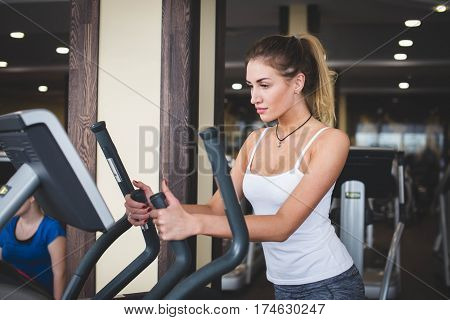 Girl doing exercises at the gym on the stepper