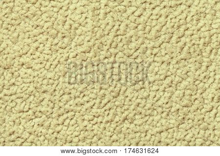 Light yellow fluffy background of soft fleecy cloth. Texture of textile closeup.