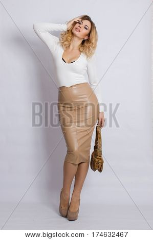 Fashion blonde woman in stylish clothes posing in the studio, holding handbag