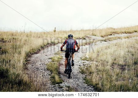 racer cyclist mountainbiker rides on trail in mountain
