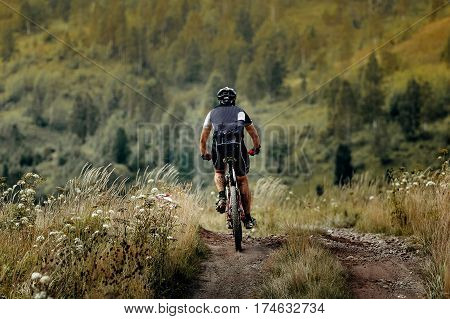 man athlete cyclist mountainbiker downhill on trail