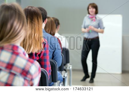 Large Group of Students from back sitting in Conference Room and listening Teacher delivering Presentation. Body of speaker is blurred focus on second female student shoulder