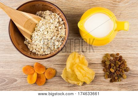 Oat Flakes, Bamboo Spoon In Bowl, Milk And Dried Fruits