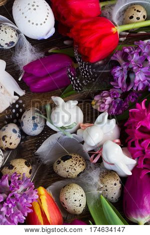 Spring fresh flowers with easter quail eggs and three white pocelane rabbits