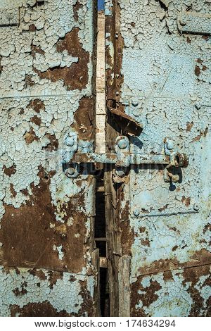 Old antique door with chipped paint and rusted lock. Macro shot.
